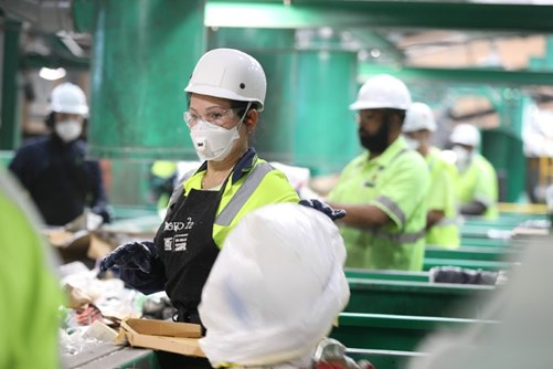 Employees of a recycling company wearing a face mask and helmet are busy thermochemically recycling waste