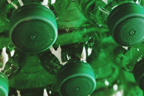 Green plastic bottles with caps hang upside down, ready to be chemically recycled