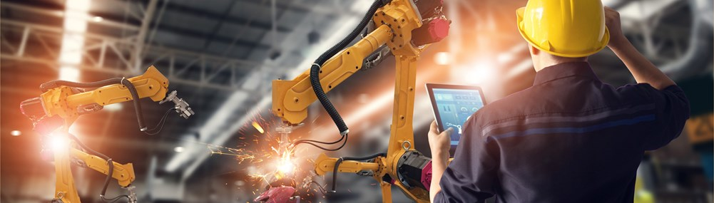 An engineer is seen programming self-operating robots in a factory.