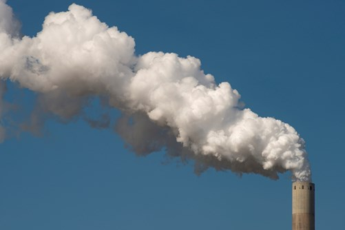 A big white cloud of smoke coming out of an industrial chimney, that can be monitored for monitoring greenhouse gas emissions with the TANGO satellite mission.