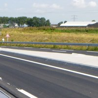 A close-up a double crash barrier with flexible foil and solar cells attached to it, as part of a pilot project along the N194 road near Heerhugowaard, The Netherlands.
