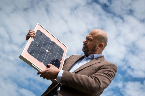 A portrait of Gianluca Coletti, Program Manager at TNO, holding the Whooper solar module in his hands.
