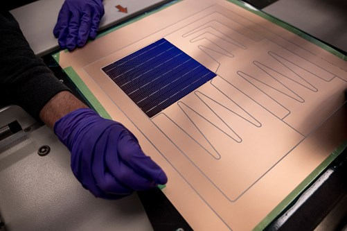 An engineer is placing a Whooper solar cel on conductive foil during the assembly.