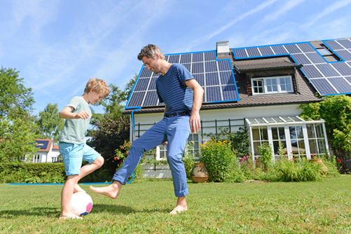 A father and son play football in the garden behind the house, on the roof are solar panels