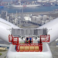 An aerial photograph of two engineers standing atop the wind turbine Haliade X with the industrial landscape of the Maasvlakte (Rotterdam, The Netherlands) on the background.