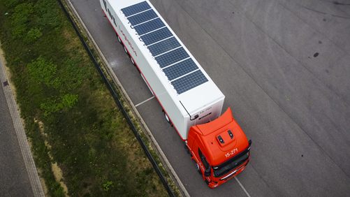 Solar panels on the roof of a white truck with a red cab